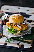Crispy chicken burger with seafood mayo, coconut chips and papaya salsa