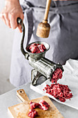 Beef is turned through a meat grinder (for beef patties)