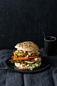 Vegan burger with fried avocado, sriracha mayonnaise and 'bacon'