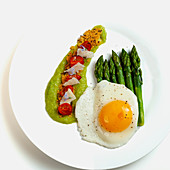 Green asparagus with fried egg, asparagus cream and confit tomatoes