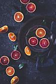 Blood oranges on a dark surface