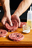 Pressing a recess into burger patties to maintain shape when grilling