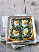 Puff pastry cake with spinach and fried eggs