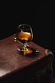 Cognac in snifter on vintage suitcase