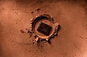 A piece of dark chocolate on cocoa powder
