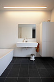 Weißes Waschbecken, Schrank und Badewanne im Badezimmer mit schwarzem Fliesenboden