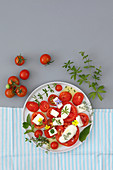 Mozzarella and tomatoes salad with herbs and edible flowers