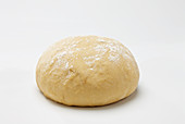 Brioche dough with flour on top on white background