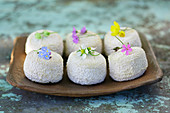 Sancerre cheese with wild flowers decoration in flat ceramic dish