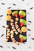 Halloween Snack-Partybuffet mit Würstchen-Mumien und Appleheads