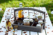 A wooden bottle carrier with apple jam, apple schnapps, apple juice and apple cider