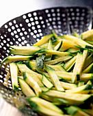 Zucchini sticks in a steamer basket
