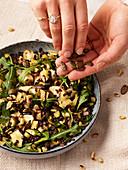 Vegan lentil salad with rocket, olives and pumpkin seeds