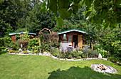 Sommerlicher Schrebergarten mit Gartenhäusern, Rasenfläche, Beeten und Feuerplatz