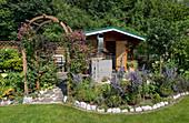 Sommerlicher Schrebergarten mit Gartenhaus, Rosenbogen mit Waldrebe 'Avant-Garde' und Staudenbeet mit zusammengebundenem Lavendel