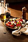 Tomato salad with black olives, mozzarella and basil