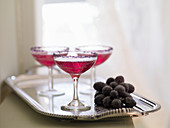 Red cocktails with sugared grapes on a silver tray