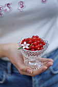Red currants in a crystal bowl in a woman's hand