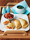 Argentine empanadas served on a tray with chilli relish