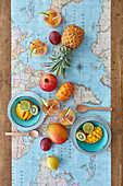 Fruity colored table with pineapple, kiwano, mango, passion fruit, lime, kiwi and pomegranate and world map