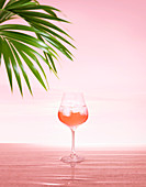 Glass of rose wine with ice on pink water and sky sunset with two palm leaves