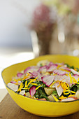 Colored salad with potato, apple, spinach, cosmos and marigold flower petals