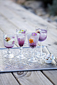 Four purple colored cocktail glasses with flower ice cubes