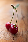 Pair of cherries on a wooden background
