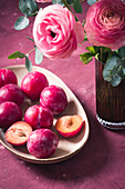 Plums on the plate and ranunculus