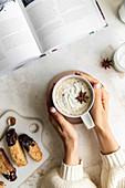 Hands holding a mug of gingerbread latte