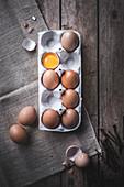 Frische Eier in Eierkarton, eines aufgeschlagen