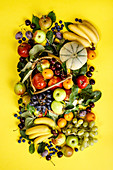 Fresh fruits and berries on yellow background