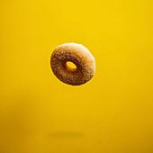 Sugar doughnut falling on yellow background