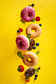 Various decorated doughnuts with sprinkles and berries falling on yellow background