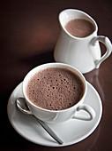 Heiße Schokolade in Tasse und Krug