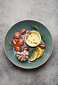 Gemüse, Kräuter, Gewürze und Olivenöl in blauem Keramikteller