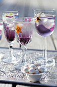 Three cocktail glasses with blueberry syrup and flowers ice cubes
