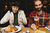 Paar beim Essen und Bier trinken