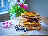 Pancakes with blueberry jam and maple syrup
