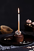 A chocolate cupcake with a lit candle