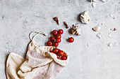 Sustainability - cherry tomatoes and garlic in a cloth bag
