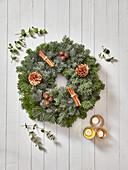 Weihnachtskranz aus Nadelzweigen mit Zapfen und Zimtstangen
