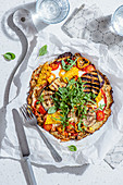 Low carb pizza made with cauliflower base, mozzarella cheese, tomatoes, aubergine, peppers, corn and rocket salad