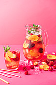 Summer fruit iced tea with peaches, raspberries, strawberries and fresh mint