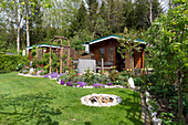 Schrebergarten mit Gartenhaus, Gerätehaus, Staudenbeet, Rasen und Feuerplatz