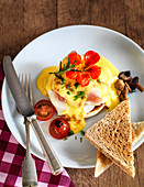 Eggs Benedict with toast tomatoes and mushrooms