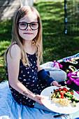 Mädchen beim Picknick mit gefülltem Teller