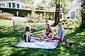 Girls having picnic in garden