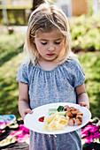 Mädchen betrachtet Essen auf ihrem Teller