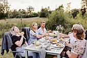 Freunde essen am Tisch im Garten